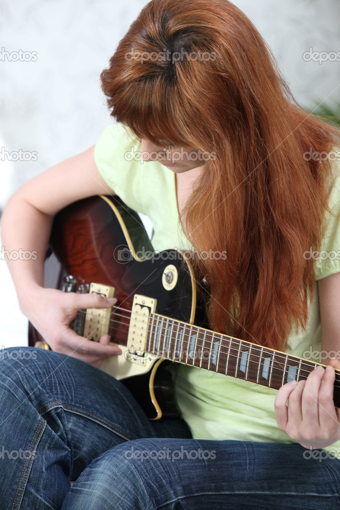 Redhead girl playing guitar — Photo #10093253