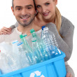 Couple recycling caret of plastic bottles - Stock Photo