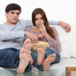 Couple eating popcorn in front of the television — Stock Photo #10100416