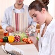Young woman reading a newspaper while her boyfriend prepares lunch - Stok fotoğraf