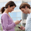 Royalty-Free Stock Photo: Couple sending text messages outside