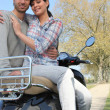 Foto Stock: Couple sitting on a bike
