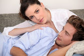 Young couple lying on a couch — Stock Photo