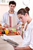 Jovem mulher lendo um jornal enquanto o namorado prepara almoço — Foto Stock