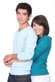 Teenage girl with arms around boyfriend — Stock Photo