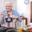 Older woman cooking a meal — Stock Photo
