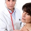 Doctor listening to a woman's chest — Stock Photo #10121212
