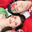 Stock Photo: Four Portuguese soccer fans laying down together