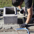 Man adjusting cinder block placement - Foto de Stock