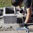 Man adjusting cinder block placement - Lizenzfreies Foto