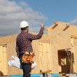 Foreman overseeing the wooden house build — Stock Photo