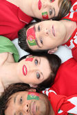 Four Portuguese soccer fans laying down together — Stock Photo