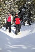 Couple skiing through the woods — Stock Photo