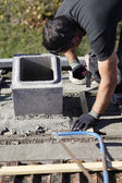 Man adjusting cinder block placement — Stock Photo