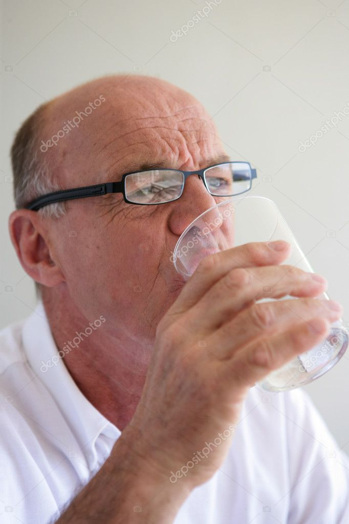 Elderly man drinking a glass of water — Stock Photo #10121252