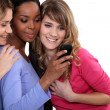 Three female friends looking at mobile telephone — Stock Photo