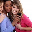Stock Photo: Three female friends looking at mobile telephone
