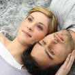 Couple lying on carpet — Stock Photo #10153678