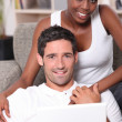 Couple sitting on sofa gray — Stockfoto