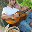 Foto Stock: Couple with guitar in the field