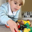 Little blond boy playing with toys — Stock Photo #10155317