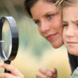 Girl with magnifying glass watching flower — Stock Photo