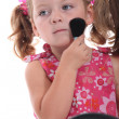 Child putting on makeup - Stock Photo