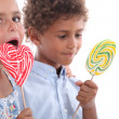 Closeup of two children eating lollipops — Photo