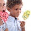 Closeup of two children eating lollipops — Stockfoto