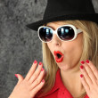 Shocked woman in sunglasses and a hat — Stock Photo