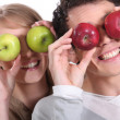 Couple holding up apples to their eyes — Stock Photo