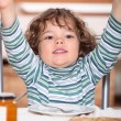 Little boy sitting at a table for a snack — Stock Photo