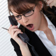 Stock Photo: Stressed womwith two telephones