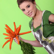 Woman with a bunch of carrots — Stok fotoğraf