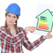 Stock Photo: Stern tradeswomgiving property energy efficiency rating of G
