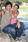 Couple sitting on the edge of a pond — Stock Photo
