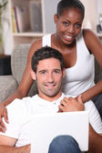 Couple sitting on sofa gray — Photo