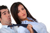 Woman pulling man's tie — Stock Photo