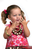An adorable little girl with plenty of jewelry. — Stock Photo