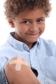 Cute boy with a plaster on his knee — Stock Photo