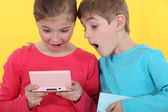 Brother and sister playing hand-held video games — Stock Photo