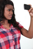 African woman taking pictures with phone — Stock Photo