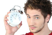 Young man with an alarm clock — Stock Photo