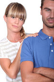 An unsure woman touching her husband's shoulder — Stock Photo