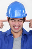 Workman putting fingers in his ears to block out noise — Stock Photo