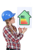 Woman holding energy-rating poster — Stock Photo