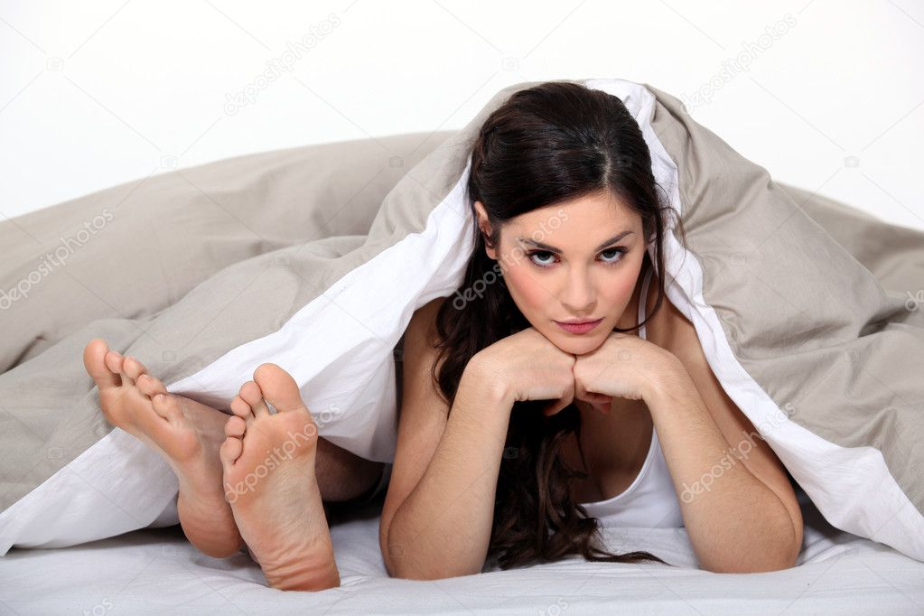 Male feet and head of a woman in bed — Stock Photo #10155153
