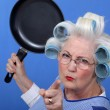 Stock Photo: Angry old womwith frying pan