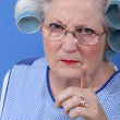 Angry woman with her hair in rollers - Stok fotoğraf