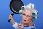 Angry old woman with a frying pan — Stock Photo